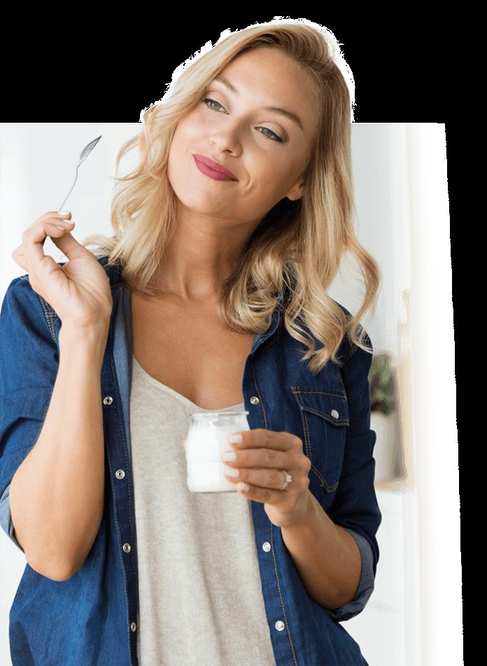 Blonde Frau mit einem Joghurtbecher und Löffel